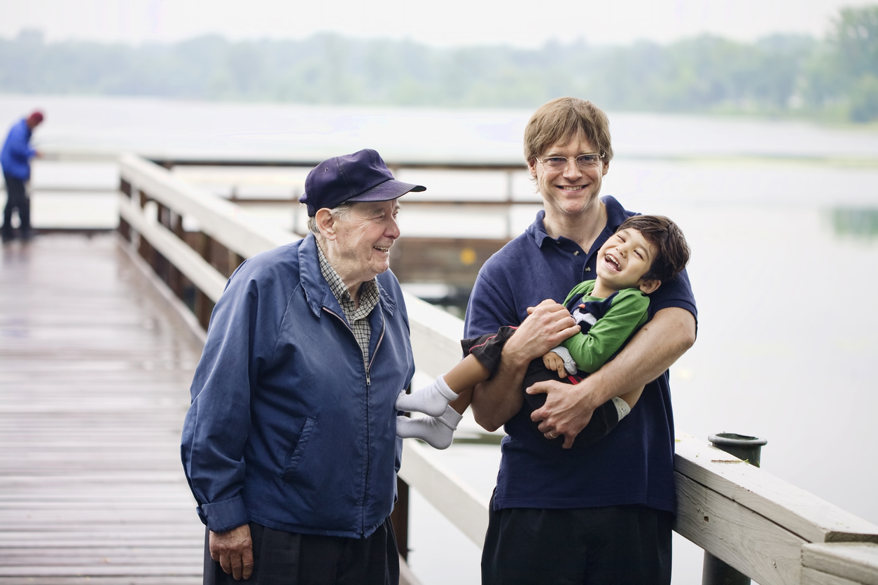 Photo of young father smiling broadly as he cradles his little son in his arms with his aged father in a baseball cap beside him smiling at the boy. They are standing on a pier looking out on a lake.