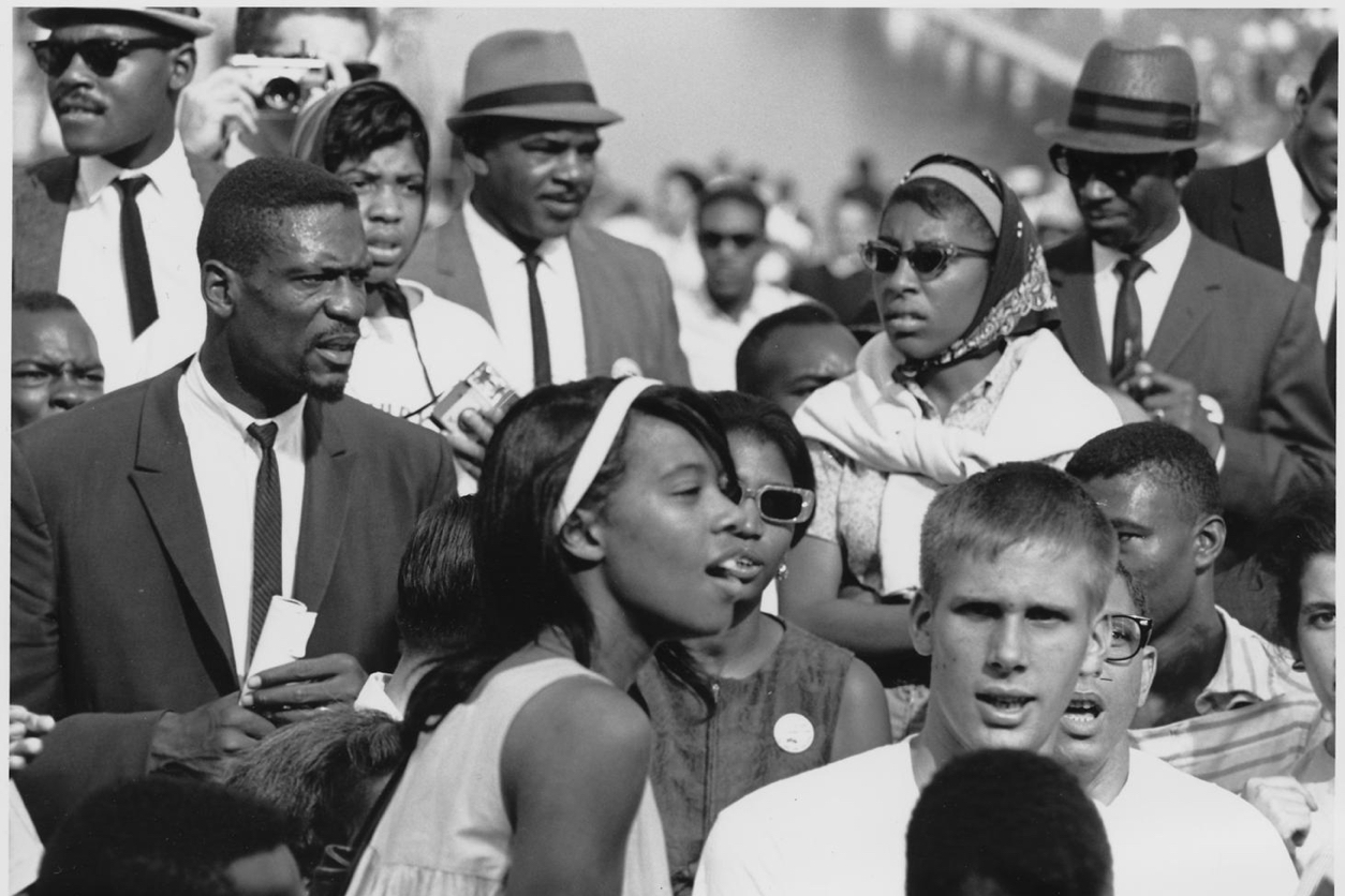 Black and white photo of a small group within a peaceful 1960s civil rights protest. The mostly black men are wearing dark suits, hats, and skinny ties. A young black woman in a sleeveless white dress looks in another direction. At front, a young white man looks at the camera seriously