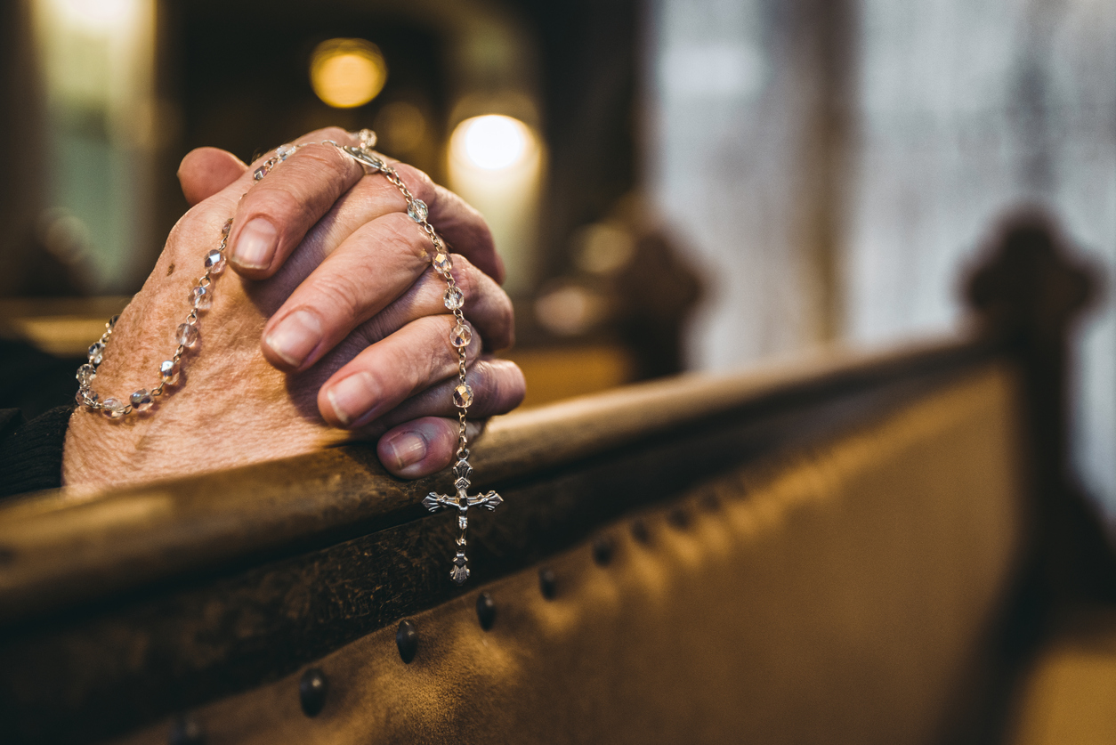 Closeup photo of two aged hands clasped in prayer, resting on a church pew, with an ornate rosary dangling from the hands.